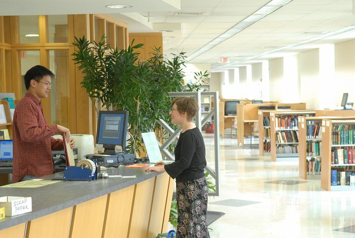 Photo of Music Library, showing circ desk with two people